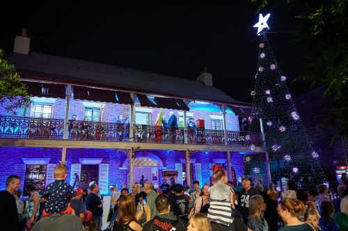 Picture of Loder House lit up next to a Christmas tree at Light Up Windsor